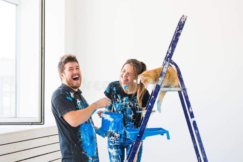 Ремонт, реновация, любимец и концепция пар любов - молодая семья с котом делая ремонт и крася стены совместно и стоковые изображения rf