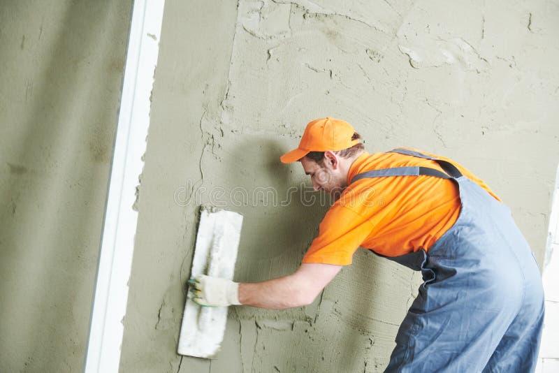 Реновация дома Штукатур приглаживая гипсолит на стене стоковая фотография rf