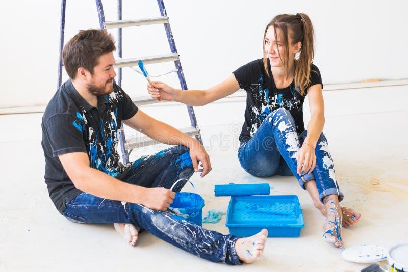Реновация, ремонт и концепция людей - портрет смешных пар запятнанных с краской над белой предпосылкой стоковые изображения rf