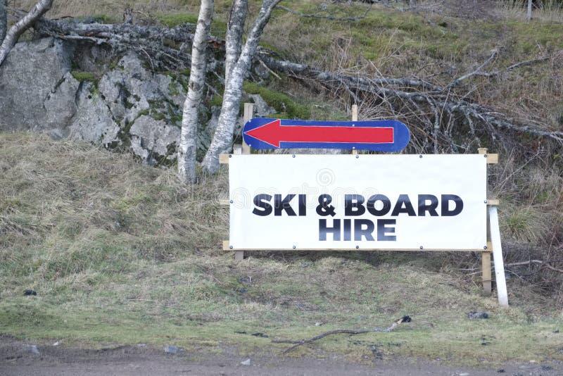 Рента лыжи и доски нанять сезонные спорт зимы подписывает дирекционную стрелку стоковое фото rf