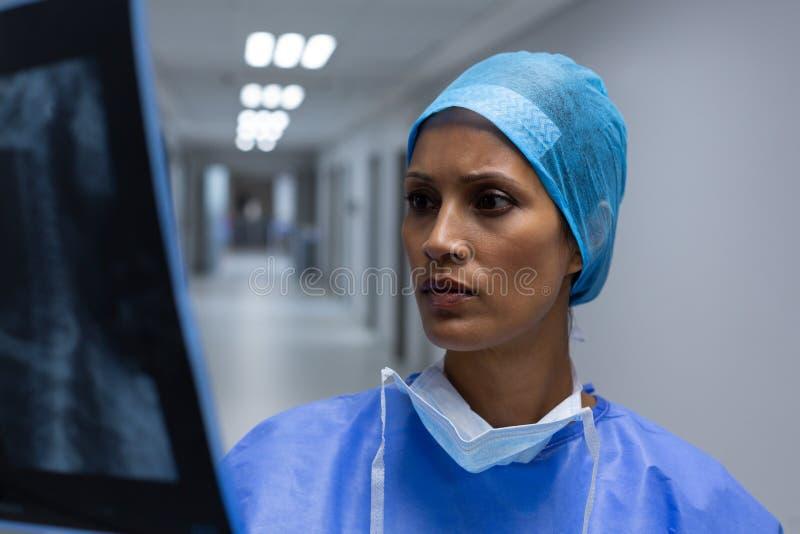 Рентгеновский снимок женского хирурга рассматривая в коридоре больницы стоковая фотография rf