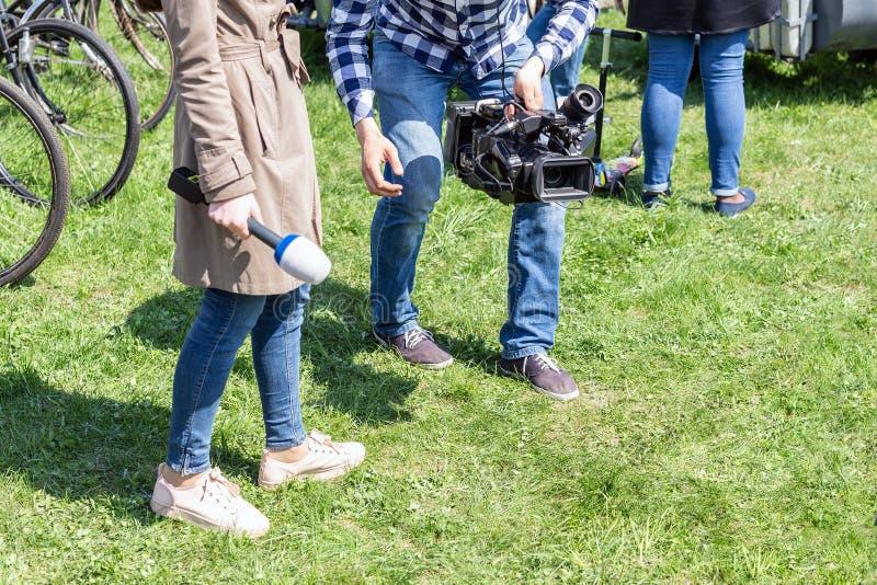 Репортеры ТВ работая outdoors Journalsit и оператор делая отчет на улице на яркий солнечный день стоковые фотографии rf