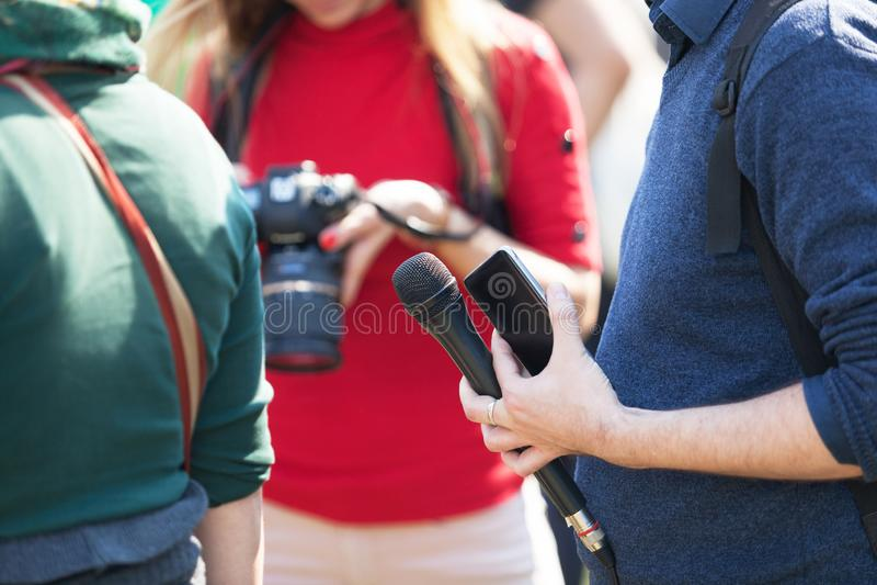 Репортер на микрофоне удерживания незначительного события, запачканн стоковое фото