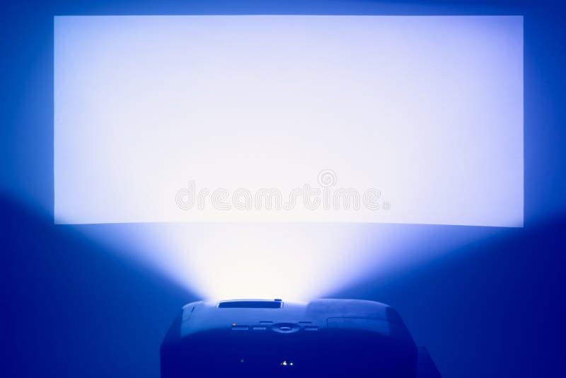 репроектор в действии с загоренным теплым голубым экраном стоковое фото