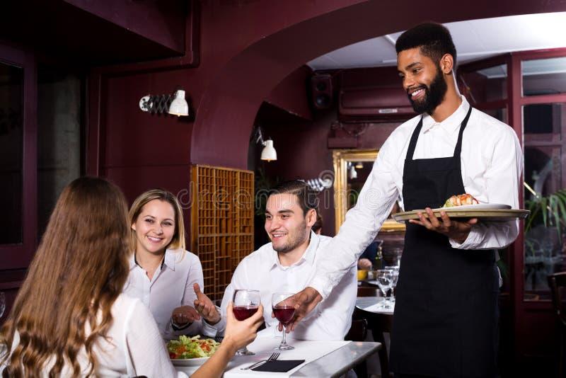 Ресторан среднего класса и жизнерадостный кельнер стоковые изображения