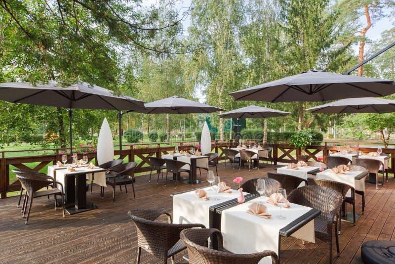 Ресторан террасы в парке, с сервировкой стола стоковые изображения rf