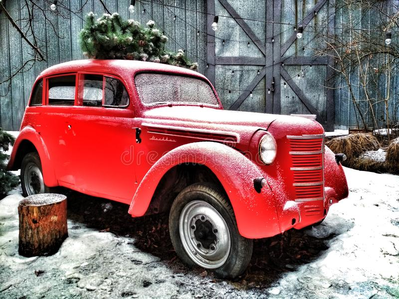 Ретро автомобиль красного цвета управляет рождественской елкой для рождества новый год темы Открытки зимы стоковые фотографии rf