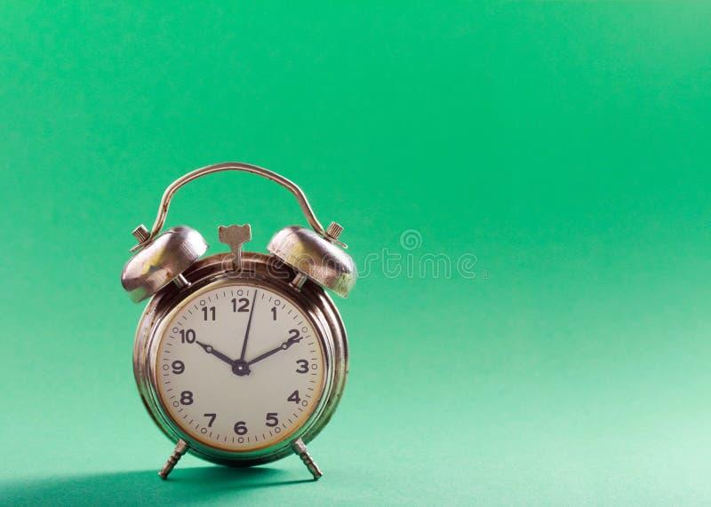 Ретро будильник над предпосылкой зеленого цвета мяты стоковая фотография rf
