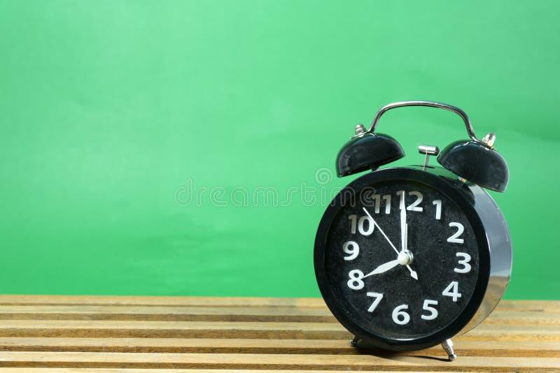 Ретро будильник на таблице на предпосылке зеленого цвета мяты стоковые изображения rf