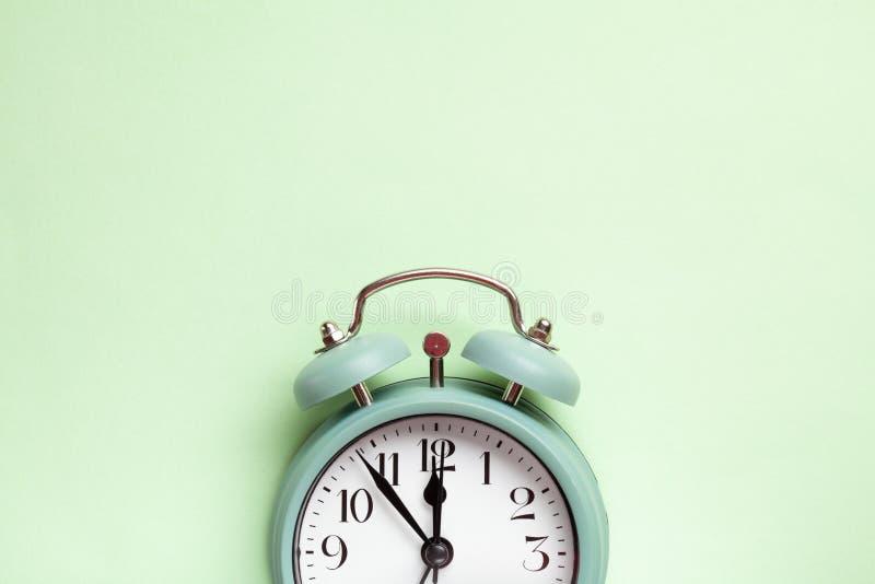 Ретро будильник стиля над предпосылкой зеленого цвета мяты стоковые фотографии rf