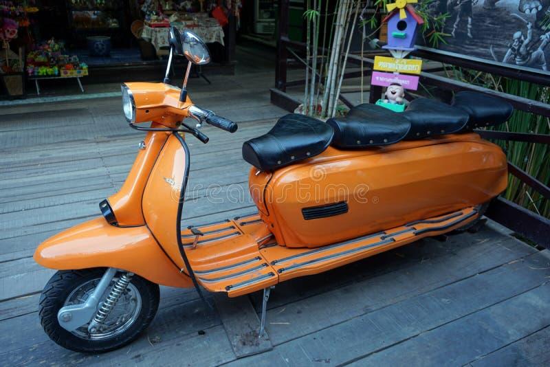 Ретро введенный в моду велосипед moto Vespa припарковал который создался для 4 мест стоковое изображение