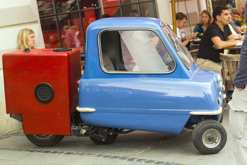 Ретро голубой мини автомобиль при красный трейлер стоя в городе стоковое фото