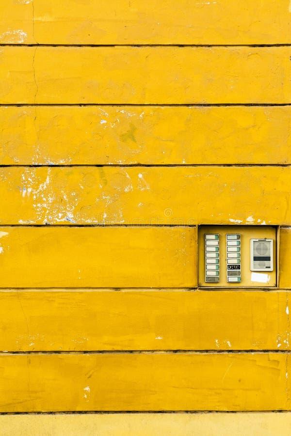 Ретро дверной звонок: электрическая внутренная связь на текстуре стены желтого цвета te стоковая фотография rf