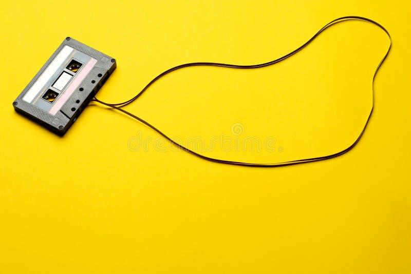Ретро кассета с лентой над желтой предпосылкой таблицы Взгляд сверху скопируйте космос стоковое изображение