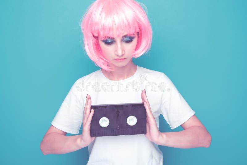 Ретро концепция fasion Женщина с розовой кассетой для пленки удерживания волос изолированной в яркой голубой студии стоковое изображение
