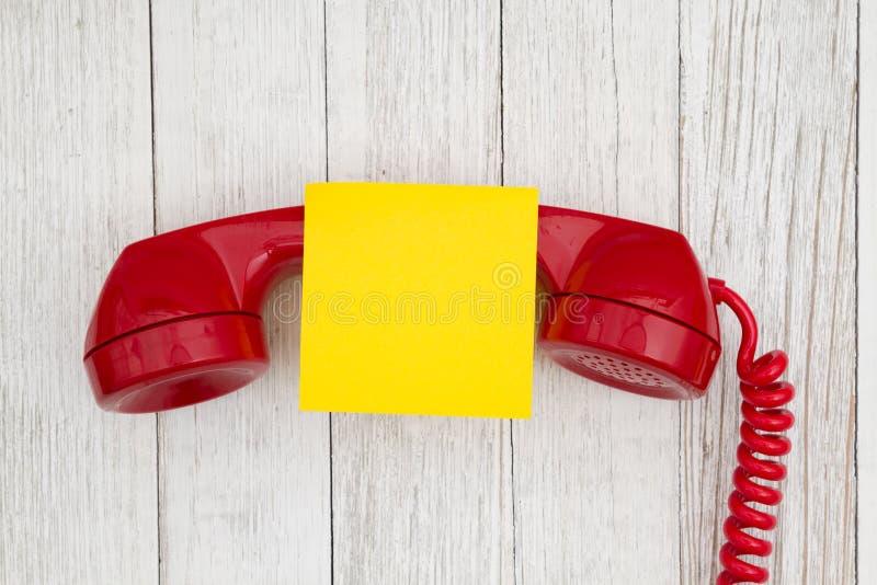 Ретро красная телефонная трубка телефона на выдержанной текстурированной побелкой предпосылке древесины стоковые изображения rf