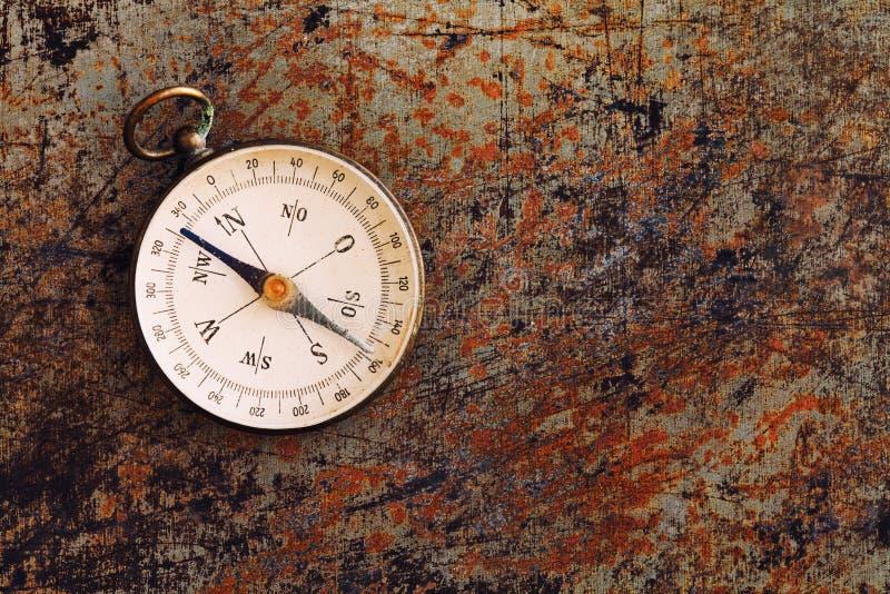 Ретро магнитный компас на текстурированной ржавой предпосылке металла Аппаратура географического исследования проводя для искать стоковые фото