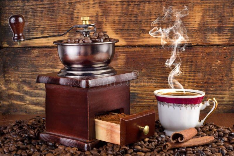 Ретро мельница и чашка кофе при черный кофе куря на деревянной предпосылке стоковое изображение rf