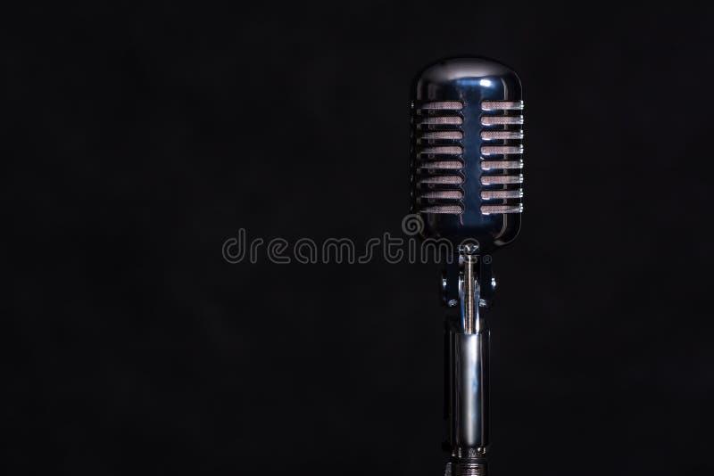 Ретро микрофон металла изолированный на темной предпосылке стоковая фотография