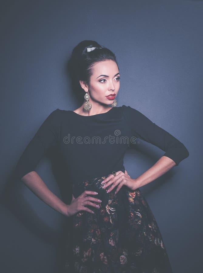 Ретро портрет женщины, стоя на черной предпосылке стоковое изображение