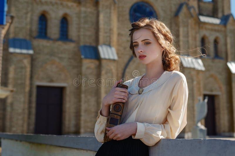Ретро портрет красивой мечтательной девушки держа книгу в руках outdoors Мягкий тонизировать года сбора винограда стоковое фото