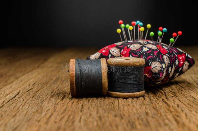 ретро поток катышкы с pincushion на деревянной доске стоковая фотография rf