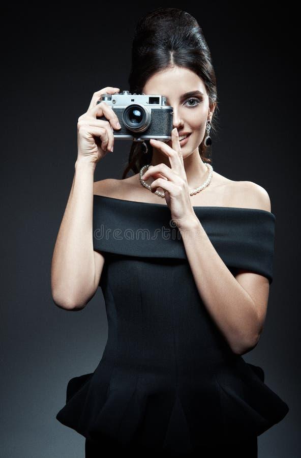Ретро съемка: красивая молодая женщина фотографируя старой камерой фильма Винтажный портрет усмехаясь шикарной девушки в стиле 60 стоковая фотография