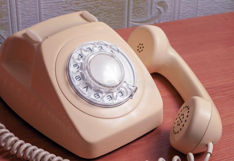 Ретро телефон на деревянном столе в передней предпосылке градиента стоковое фото