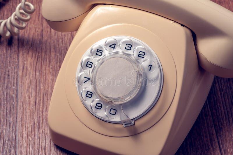 Ретро телефон на деревянном столе в передней предпосылке градиента стоковая фотография rf