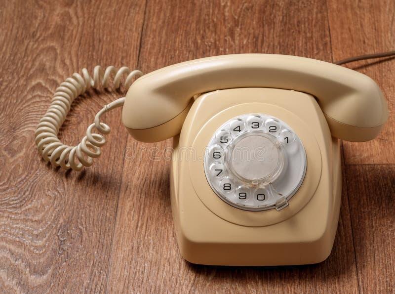 Ретро телефон на деревянном столе в передней предпосылке градиента стоковые изображения rf