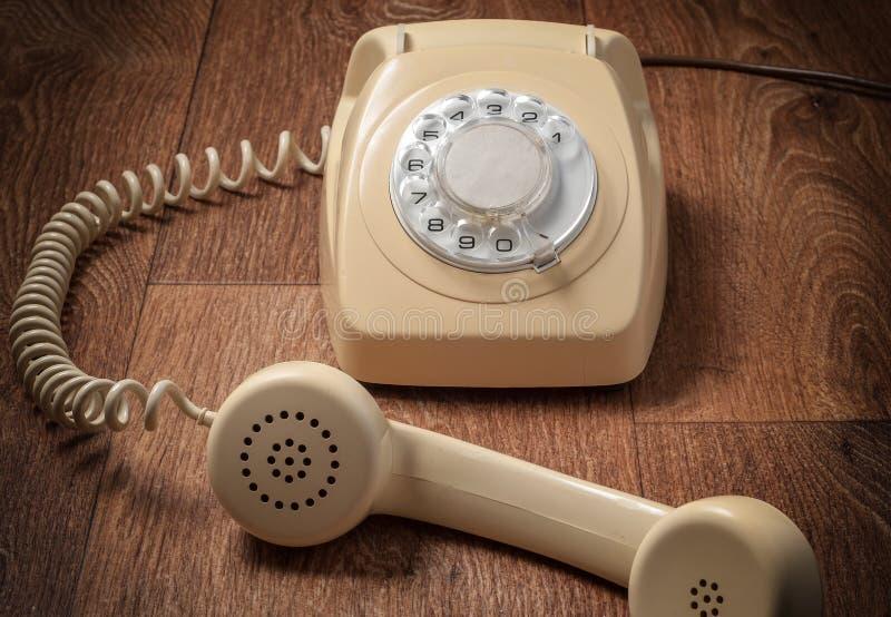 Ретро телефон на деревянном столе в передней предпосылке градиента стоковые фотографии rf