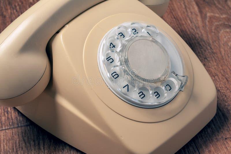Ретро телефон на деревянном столе в передней предпосылке градиента стоковое изображение