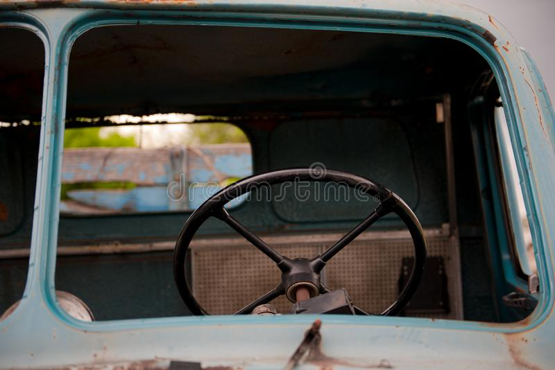 Ретро черное рулевое колесо внутри старой и покинутой голубой тележки стоковые изображения