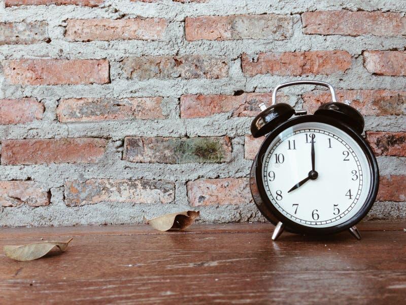Ретро черный будильник и сушит листья на деревянном столе стоковая фотография