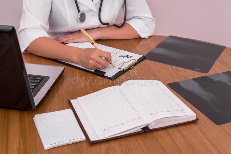 Рецепт доктора заполняя с рентгеновским снимком пациента на деревянном столе стоковая фотография rf