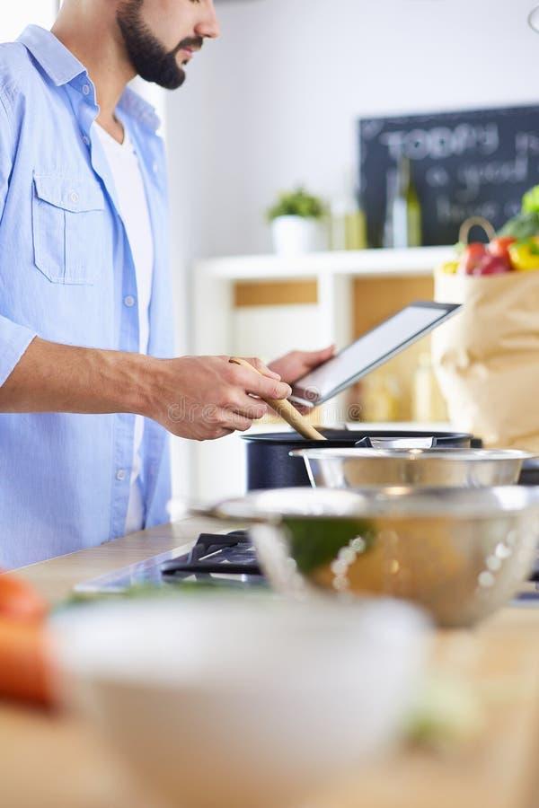 Рецепт человека следовать на цифровом планшете и варить вкусную и здоровую еду в кухне дома стоковое фото