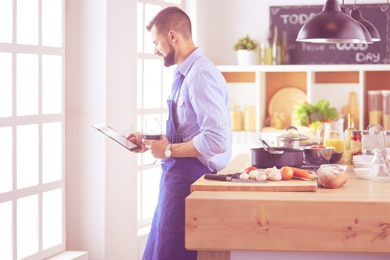 Рецепт человека следовать на цифровом планшете и варить вкусную и здоровую еду в кухне дома стоковые фото