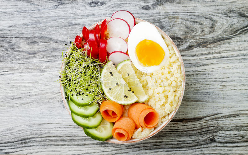 Рецепт шара Будды вытрезвителя Veggies с яичком, морковами, ростками, кускус, огурцом, редисками, семенами Взгляд сверху, плоское стоковая фотография