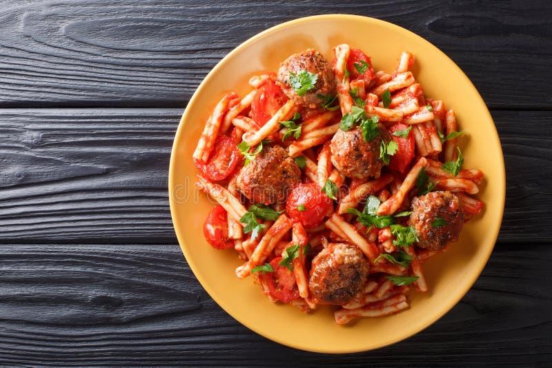 Рецепт Casarecce макаронных изделий с шариками, травами и сыром мяса в крупном плане томатного соуса на плите r стоковые фотографии rf