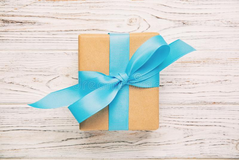 Рециркулированная бумажная подарочная коробка с голубой лентой на старой деревянной белой предпосылке Тонизированный год сбора ви стоковые изображения rf