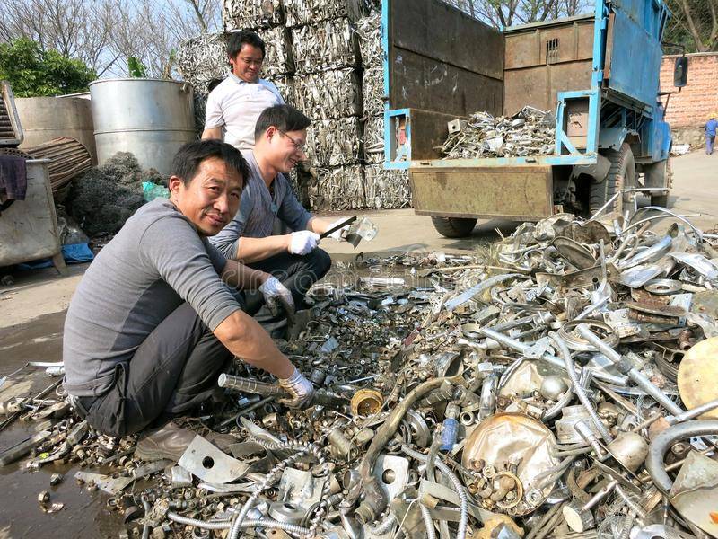 Рециркулировать металла - люди работая в рециркулировать центр стоковое изображение