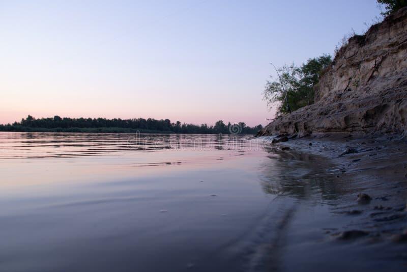 Речной берег в заходе солнца молчаливая вода и желтый песок стоковое изображение