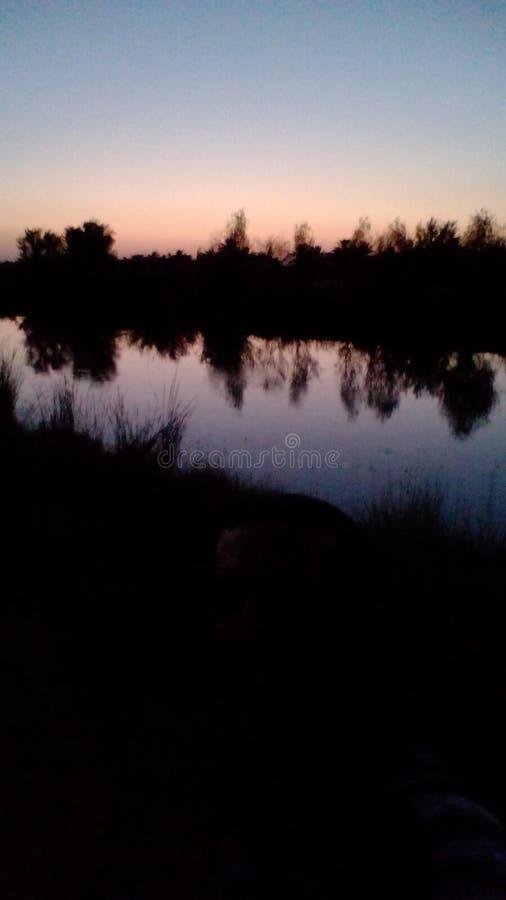 Речной берег на сумраке стоковое изображение