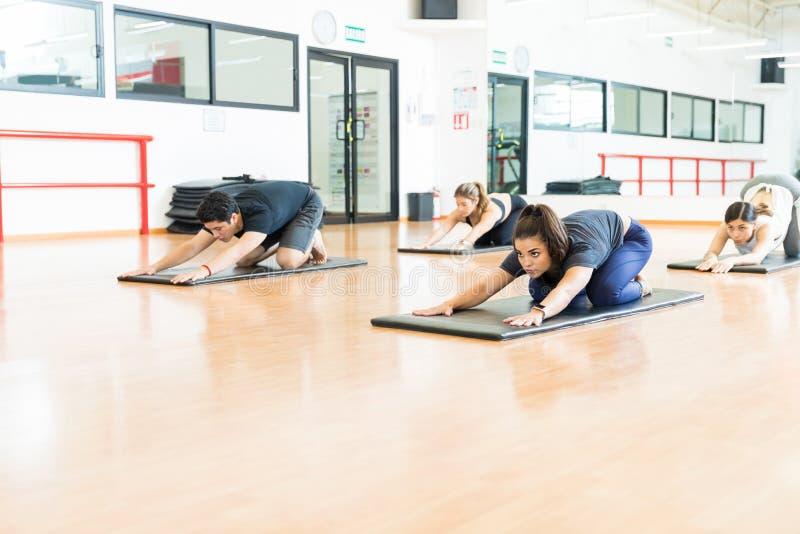 Решительно женщины и человек делая йогу на циновках в спортзале стоковое фото rf