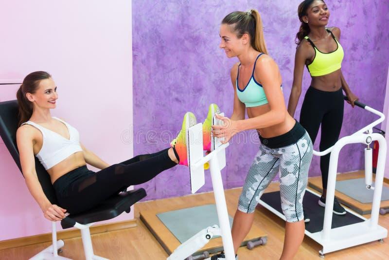 Решительно женщины пригонки работая под наведением опытного инструктора фитнеса стоковое фото