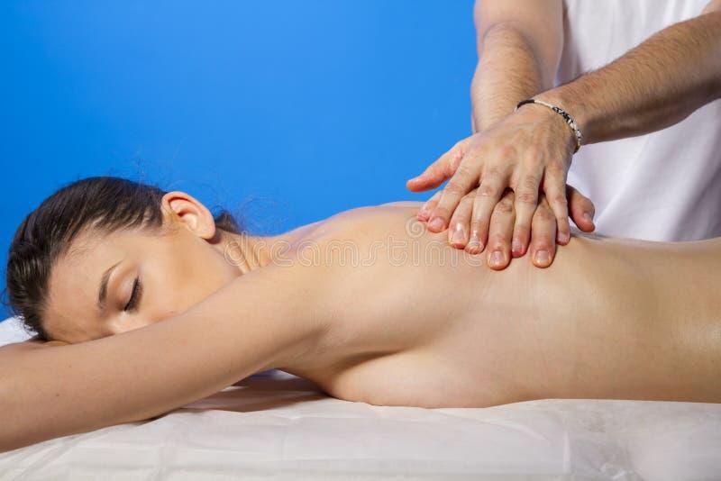 Релаксация. Masseur делая массаж на теле женщины в салоне курорта стоковые изображения rf