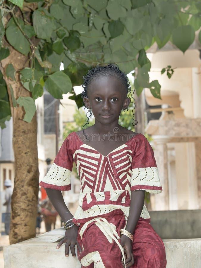 Редакционный титр: M'Bao, †«6-ое августа 2014 Сенегала, Африки: Ребенок в улице на праздник стоковая фотография