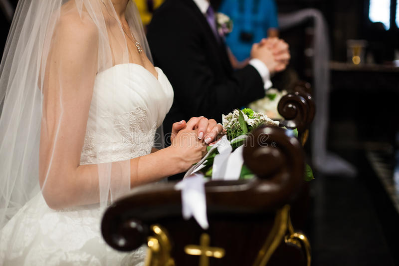 Религиозный жених и невеста моля в церков на свадебной церемонии стоковые изображения