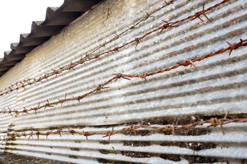 Ржавая загородка металла колючей проволоки и цинка стоковые фото