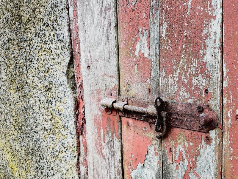 Ржавая защелка двери на красной двери стоковая фотография